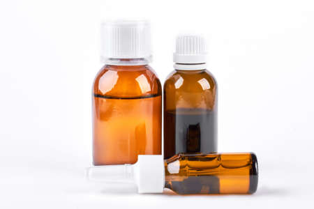 Bottiglie con medicina, spray nasale. Sciroppo per la tosse, sciroppo antipiretico e gocce di naso su sfondo bianco. Farmaci per il trattamento a freddo. Archivio Fotografico