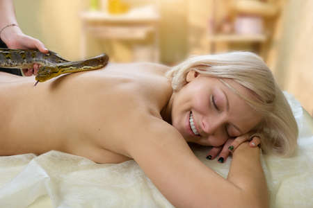 Beautiful woman with a snake in spa salon. Smiling blonde woman receiving snake massage in spa salon.
