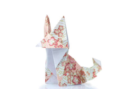 Cute fox origami figurine. Animal model made of folded paper with pattern. Easy hand crafting, DIY. Stock Photo
