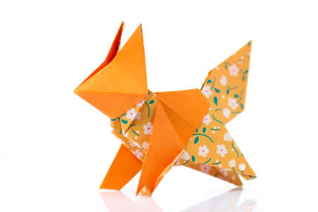Fox origami model on white. Folded orange and patterned paper. Artwork of talented child. Stock Photo