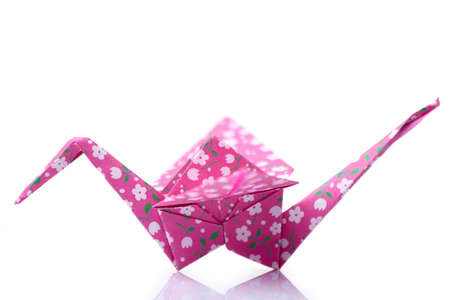 Pink orizuru figurine on white. Classic Japanese design of paper crane. Origami crafting, art lessons, culture.