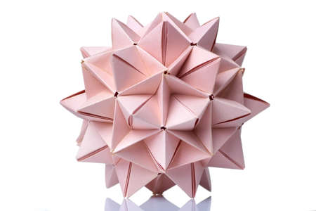 Spiky ball origami model. Wonderful figurine made of pink colored paper and assembled of many units.