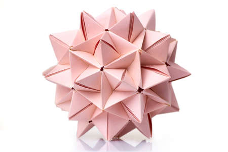 Multi piece spiky origami ball on white background. Complex geometry and advanced skills of folding paper. Stock Photo