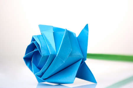 Beautiful blue flower origami. Learning art of folding paper. Childs project dedicated to International Womens day. Stock Photo
