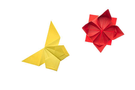Yellow butterfly and red flower on white. Simple origami models, folding paper art. Hand crafting for children. Фото со стока