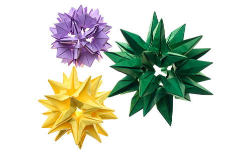 Flower kusudama models on white. Yellow, green and violet origami crafts made by young artist. Cool art projects.