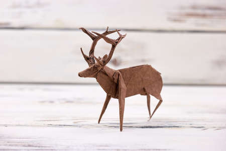 Deer figurine on wooden background. Beautiful handmade art, origami or paper folding. Crafts and creative skills.