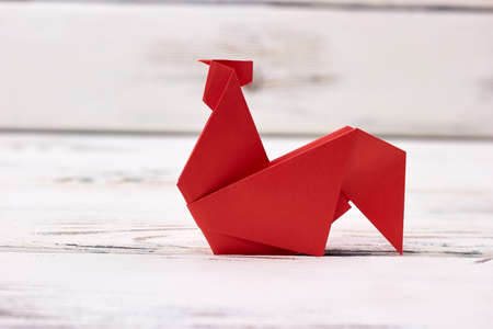 Simplified rooster origami model. Folded red paper into bird shape. Creative project of beginner child.