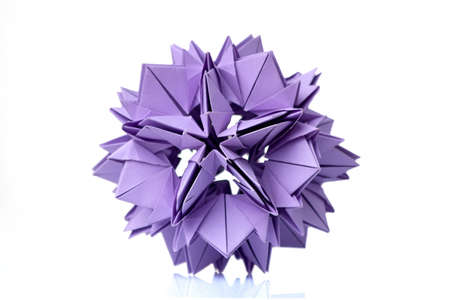 Violet flower origami on white. Wonderful figurine made of folded colorful paper. Piece of craftsmanship. Stock Photo