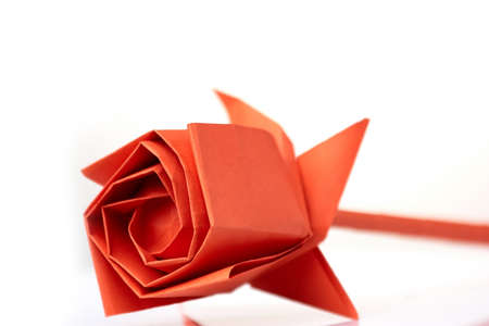 Rose flower made of paper. Beautifully folded bulb, made of red paper. Origami crafting project for beginner. Stock Photo