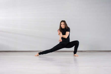 Cute girl dancing modern dance. Young slim woman performing contemporary dance on studio background.