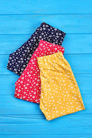 New folded baby girl pants. Setting of colorful baby girl leggings, vertical image. Modern kids apparel on sale. Stock Photo