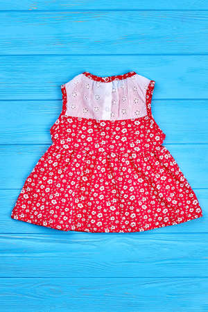 Beautiful vintage baby-girl dress. Natural childs red sleeveless dress on sale. Little girls summer clothing, top view. Stock Photo
