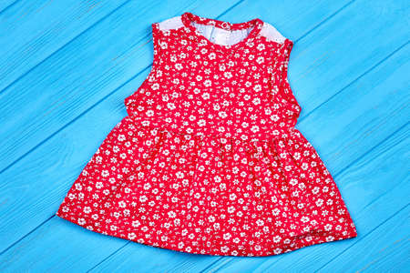 Red cotton baby-girl summer dress. Beautiful infant girl dress with pattern of white small flowers on blue wooden backgrond. Natural baby dress on sale.