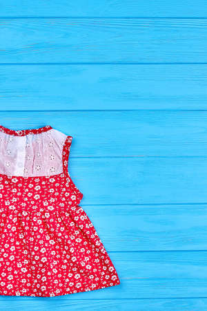 Baby red dress with a pattern of flowers. Organic baby summer dress and copy space, vertical image. Stock Photo