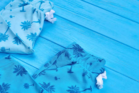 Close up of casual cotton baby clothing. Toddler baby natural spring or summer leggings in detail, blue wooden background.