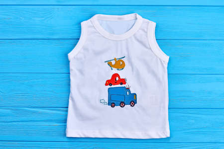 Baby boy white t-shirt print design. Toddler boy cotton t-shirt with transport illustration, blue wooden background. Stock Photo
