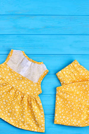 Summer clothing for infant girl. Toddlers cotton yellow suit and copy space. Casual little girl natural apparel, top view. Stock Photo