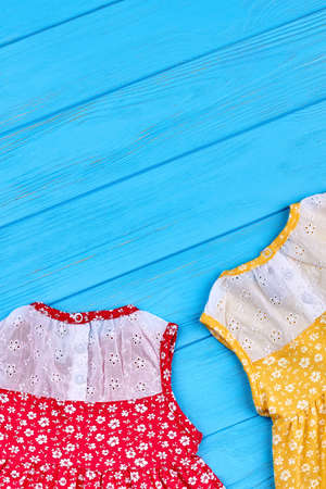Casual baby dress and copy space. Vintage design little girls summer dresses on blue wooden background. Colored summer baby apparel. Stock Photo