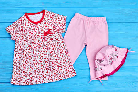 Beautiful collection of baby-girl clothes. Toddler girl cotton dress, leggings and hat on blue wooden background. Infant girl summer outfit.