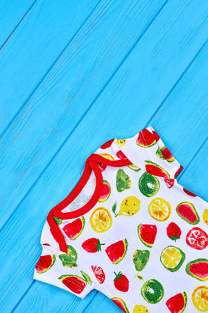Dainty design baby summer outfit. Top view of trendy printed clothes for toddler girls, blue wooden background.
