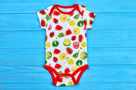 Cute fruit design baby bodysuit. Unisex short sleeve cotton baby romper on colored wooden background. Newborn summer outfit. Stock Photo