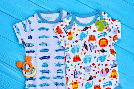 Infant baby cotton summer bodysuits. Baby dainty design organic garment and accessories on wooden background, top view. Newborn summer apparel.