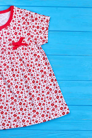 Cropped image of natural baby dress. Toddler girl retro print summer wear close up. Baby summer gown with pattern of small red flowers. Stock Photo