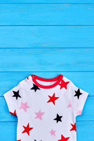 New cotton apparel for kids. Star print white t-shirt for toddler baby, copy space. Childs summer natural clothes.