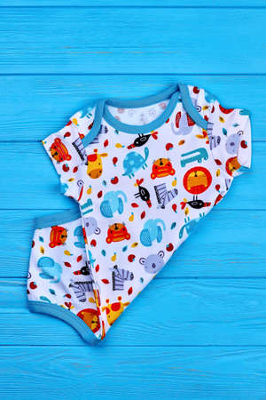 Top quality patterned baby bodysuit. Toddler boy new cotton printed romper on colored background. Baby kids summer fashion.