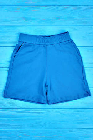 Infant boy short cotton pants. Summer baby colored clothing, wooden background. Children casual summer shorts on sale. Stock Photo