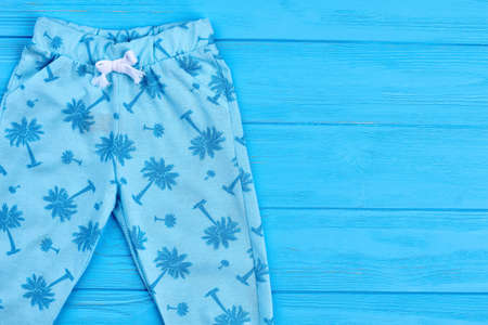New fashion design baby leggings. Fashionable printed light blue pants for baby-girls, copy space. Modern trousers for little girls on blue wooden background.