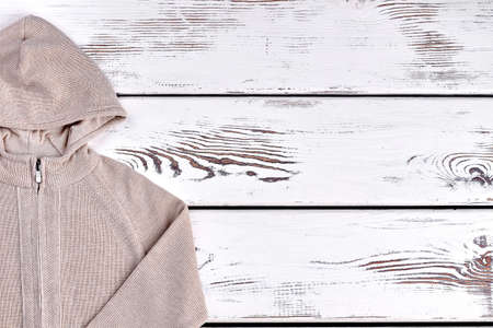 Boys hooded warm beige sweater. Beige cardigan with hoodie for childrens, copy space. Winter fashion garment for boys. Stock Photo