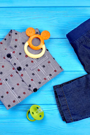 Modern denim clothes for baby-boy. Set of cotton shirt and jean trousers, accessories for little boy, top view. Set of trendy denim clothes for baby-boy. New autumn apparel for infant boy.