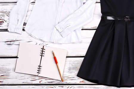 Girls school clothes and accessories. White cotton blouse, black dress, paper notebook, pensil. Girls neccessary things for school. Stock Photo