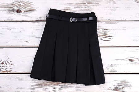 Pleated black uniform skirt. Black cotton belted skirt with pleats on white wooden background. Girls new school skirt.