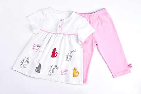 Newborn girl beautiful summer clothes. Infant girl set of white cartoon dress and pink leggings. Baby-girl cute summer garment on sale.