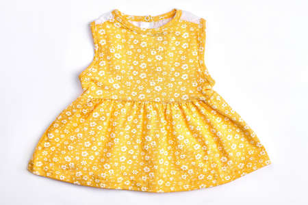 Baby-girl yellow patterned top. Newborn baby girl cotton sleeveless dress with a pattern of small white flowers, white background. Infant girl summer clothes. Stock Photo