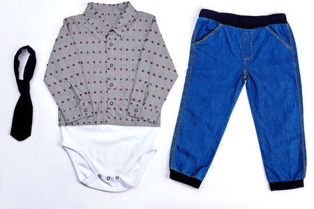 Set of modern apparel for baby-boy. Toddler boy fashion dotted bodysuit, black tie and denim jeans. Infant boy collection of autumn modern garment.