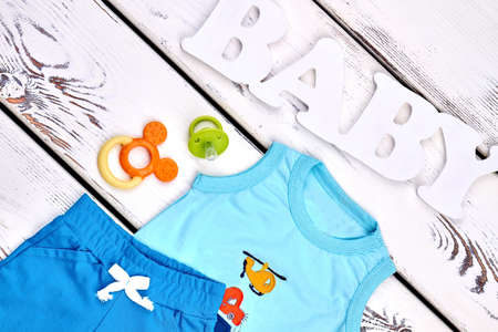 Toddler boy modern summer apparel. Little boy high quality textile shorts, sleeveless cartoon t-shirt, accessories. Baby boy summer outfit background. Stock Photo