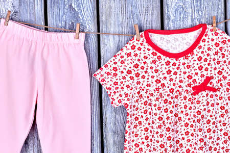 Kids clean apparel on clothesline. Infant girl fresh trousers and dress drying on rope on grey wooden background. Kids apparel in laundry. Stock Photo