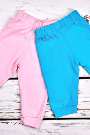 Kids new casual trousers. Baby spring or summer colored pants on wooden background, top view. Shop childs outfit.