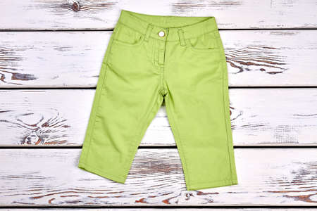 Little girl beautiful green trousers. Baby-girl cute trendy pants on white wooden background. Kids fashion apparel.