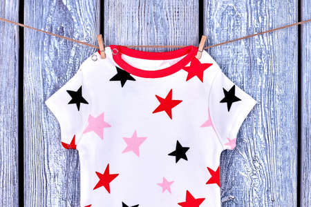 Infant baby printed t-shirt on rope. Newborn kids patterned clothes hanging on clothesline on old wooden background. Stock Photo