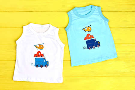 Bab boy collection of t-shirts. Infant boys cartoon sleeveless t-shirts on yellow wooden background. Childs high quality apparel on sale. Stock fotó