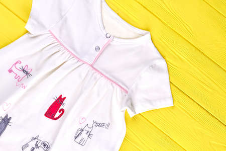 Little girl white printed top. Baby-girl cute cotton sundress on yellow wooden background, top view.