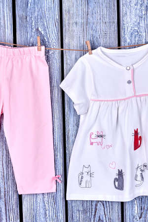 Baby-girl apparel on clothesline. Infant girl casual garment hanging on rope on old wooden background. Concept of kids clothes cleanness.