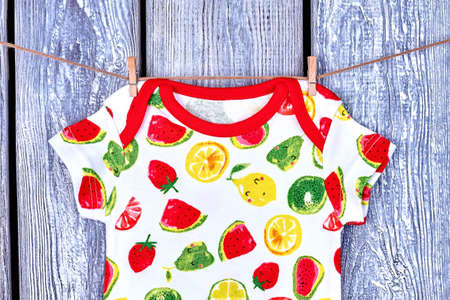 Baby t-shirt hanging on rope. Newborn baby fruit print bodysuit drying on clothesline on wooden background.