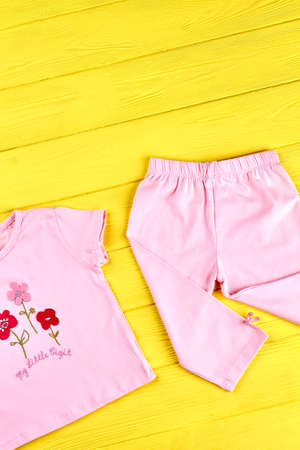 Childs beautiful pink outfit. Infant girl brand organic clothes on yellow wooden background. Kids summer garment.