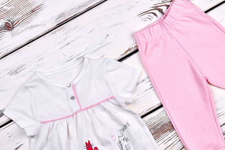 Toddler girl cute cotton suit. Infant girl white beautiful top and pink pants on wooden background. Kids brand clothes on sale.